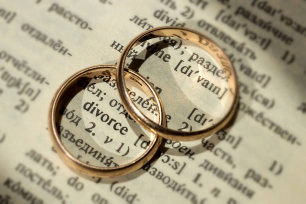 "two separate wedding rings next to the word ""divorce"". the concept of divorce, parting, infidelity . selective focus. - divorzio foto e immagini stock"