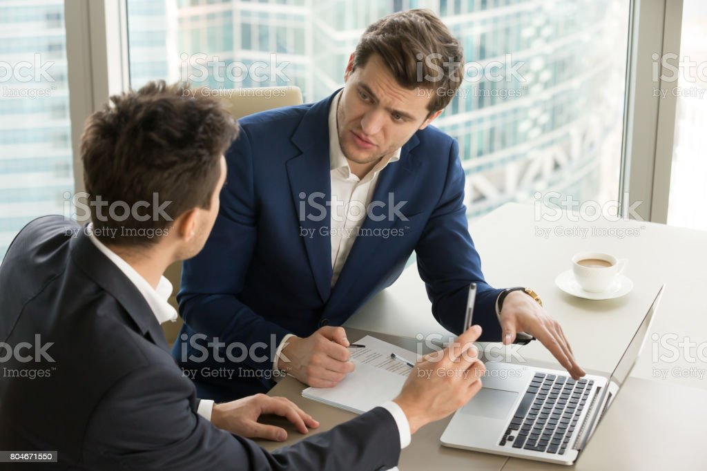 Two serious businessmen using laptop, discussing new project at office stock photo