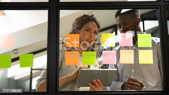 1085713886 istock photo Two serious coworkers checking project plan writing on sticky notes 1171786282