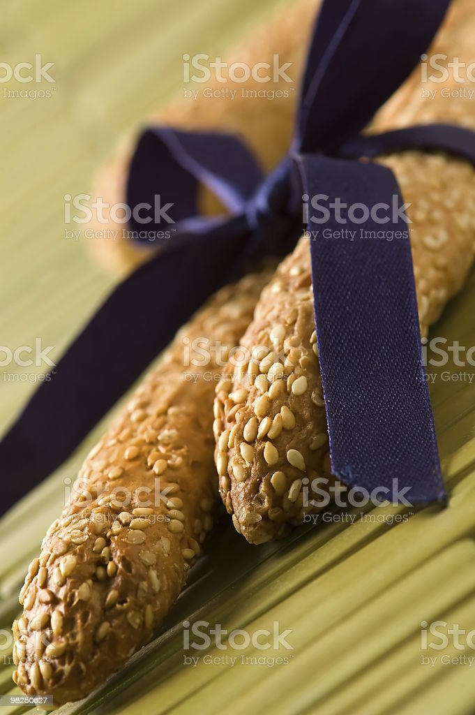 Two sesame breadsticks tied with purple ribbon royalty-free stock photo