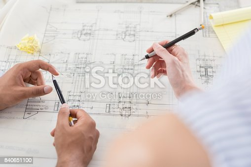 istock Two sets of hands work on architectural drawing together 840651100