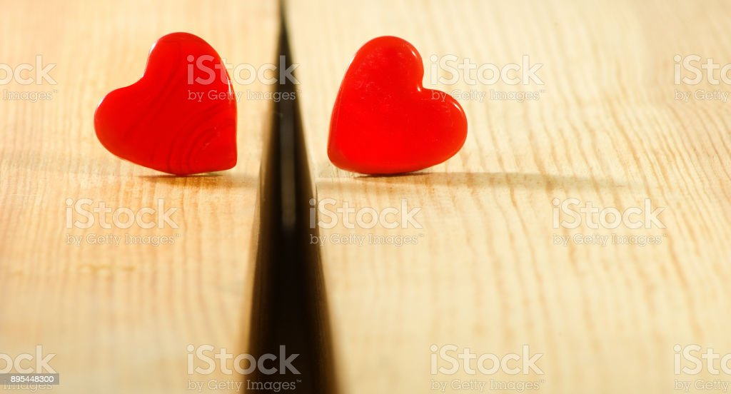 two severed hearts on wooden table close-up stock photo