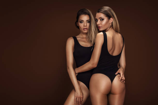 zwei sexy attraktive zwillinge frauen posieren - sinnlichkeit stock-fotos und bilder