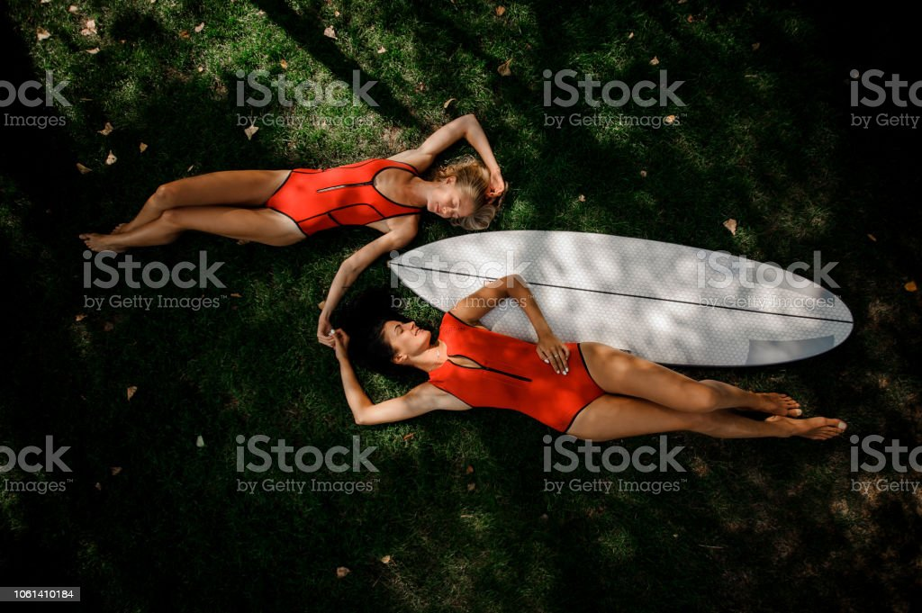 Two girls, blonde and brunette, in red swimsuits lying on the two...