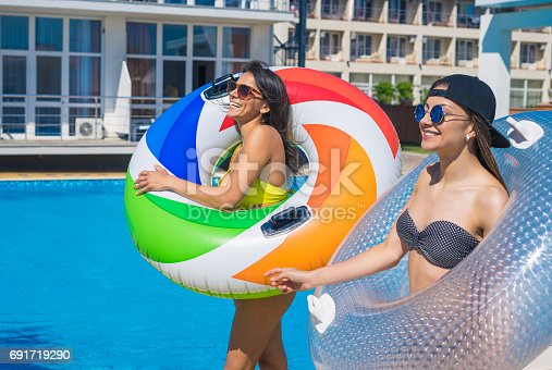 700603062istockphoto Two sexy girls walking with swimming circles near swimming pool 691719290