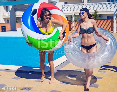 700603062istockphoto Two sexy girls walking with swimming circles near swimming pool 691719326