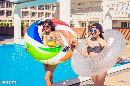 700603062istockphoto Two sexy girls walking with swimming circles near swimming pool 695612178