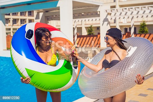 700603062istockphoto Two sexy girls walking with swimming circles near swimming pool 695612230