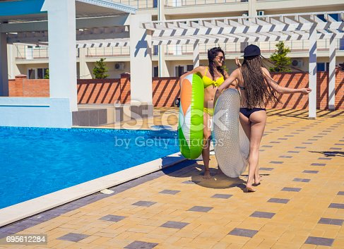 700603062istockphoto Two sexy girls walking with swimming circles near swimming pool 695612284