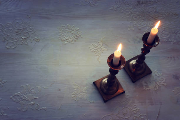 two shabbat candlesticks with burning candles over wooden table. top view. low key stock photo