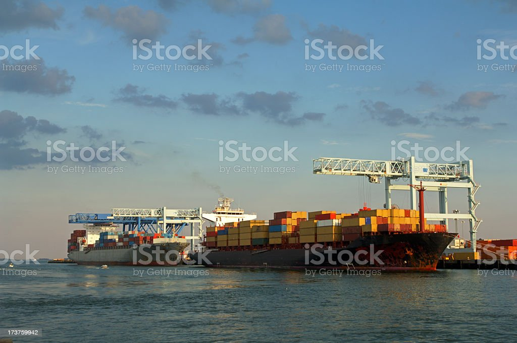 Two ships full of containers near a port under a blue sky stock photo