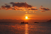 Two ships floating towards each other on background of red sunset