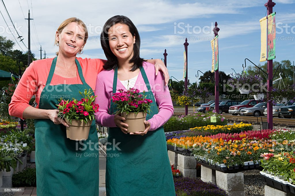 Two shop assistants holding flowers stock photo