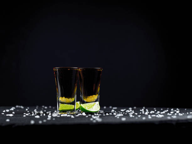 Two shots tequila gold with juicy lime and sea salt on a dark background Two shots tequila gold with juicy lime and sea salt on a dark background tequila shot stock pictures, royalty-free photos & images
