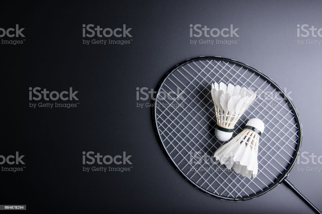 Two shuttlecocks and badminton racket on black background.Sport concept, Copy space image for your text. stock photo