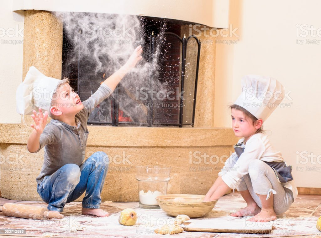 Two siblings - boy and girl - in chef's hats near the fireplace sitting on the kitchen floor soiled with flour, playing with food, making mess and having fun stock photo