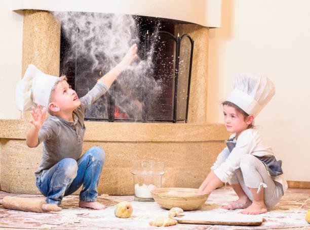 zwei geschwister - jungen und mädchen - in kochmützen am kamin sitzen auf dem küchenboden verschmutzt mit mehl, mit essen spielen, chaos und spaß haben - anti unordnung stock-fotos und bilder