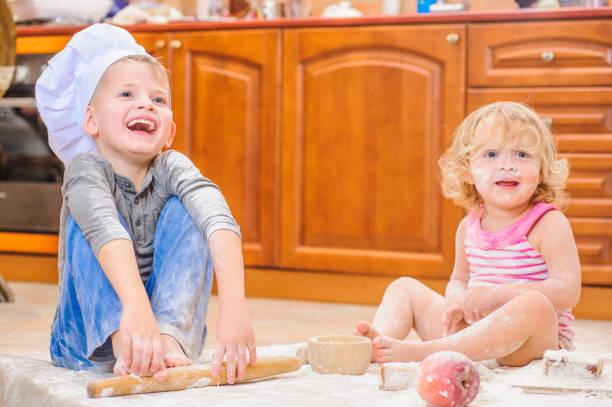 zwei geschwister - jungen und mädchen - in kochmützen sitzen auf dem küchenboden verschmutzt mit mehl, mit essen spielen, chaos und spaß haben - 3 zutaten kuchen stock-fotos und bilder