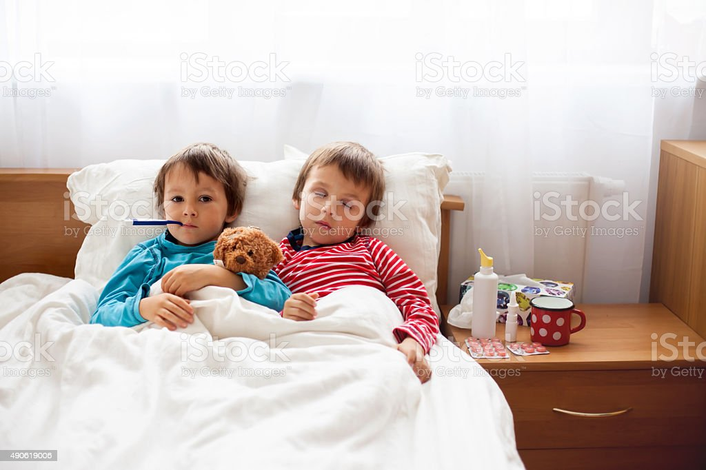 Two sick boys, brothers, lying down in bed with fever stock photo