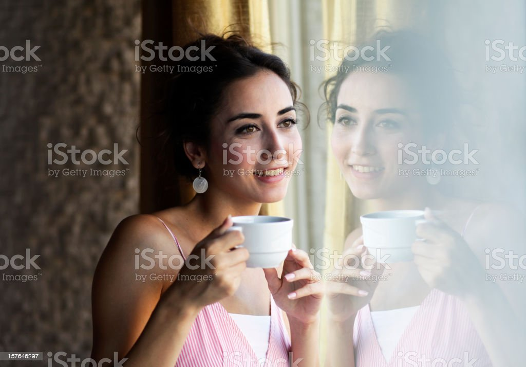 Confident beautiful young woman enjoying her coffee front of a window,