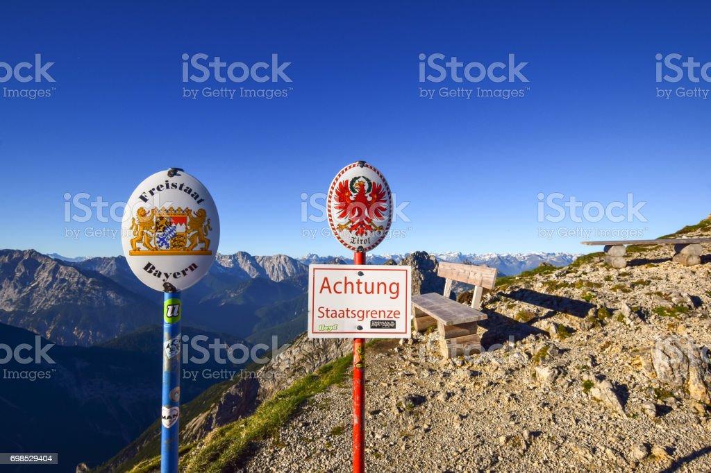 Zwei Zeichen Beiträge an der Grenze zwischen dem Bundesland Bayern und dem österreichischen Bundesland Tirol liegt auf einem Bergrücken im Karwendelgebirge in den Alpen. Warnschild: