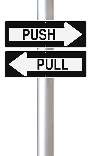 Two signs with arrows signaling push and pull Modified one way street signs indicating Push and Pull pulling stock pictures, royalty-free photos & images