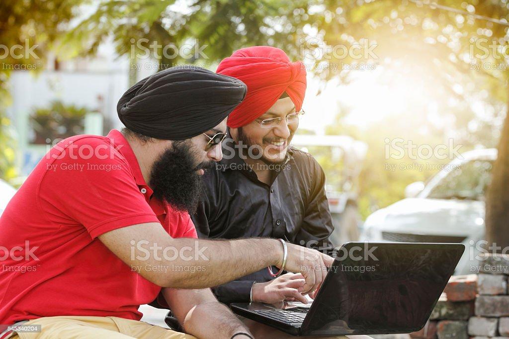 Two Sikh men using laptop stock photo