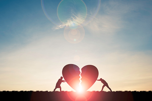 Two silhouette men pushing broken heart with sunlight and blue sky , Valentine 's day concept.