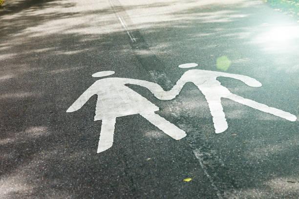 Zwei Silhouetten einer Frau und eines Kindes auf einem leeren Fußweg in einem Park.. Elternleitkonzept - Fußgängerschild auf dem Bürgersteig – Foto