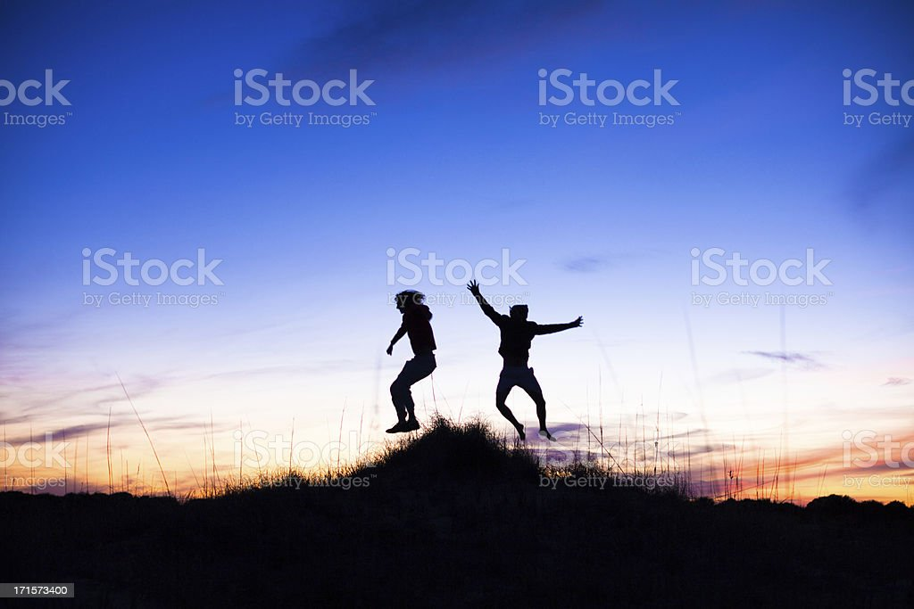 Two Silhouettes of males jumping on beach at sunset royalty-free stock photo