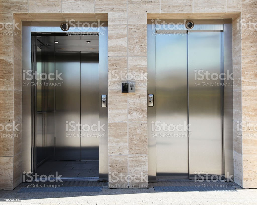 Two silver elevators side by side next to beige wall stock photo
