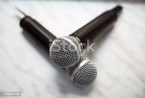 istock Two silver microphones isolated over white background . Two wireless microphones on the conference table. 1132941162