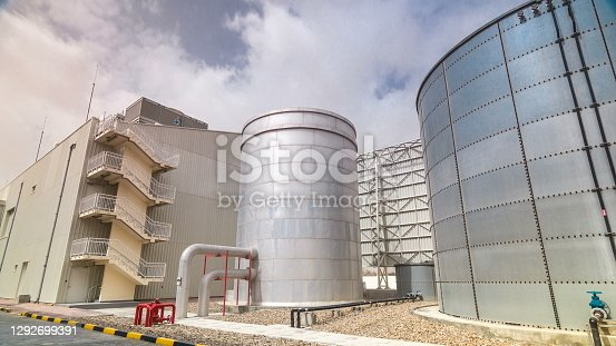 Two silver Water Tanks with fence timelapse . Cooling system. Cloudy sky