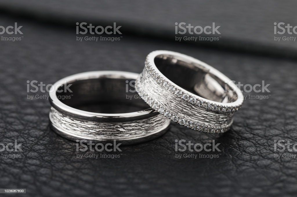 Two Silver Wedding Rings On Black Leather Background Stock Photo