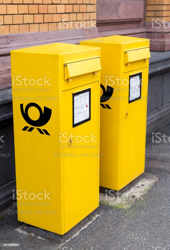 Two similar yellow letter boxes standing in a row on the ground stock photo
