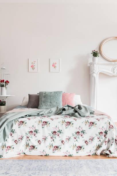zwei einfache rosa plakate hängen an der wand über dem bett mit kissen und floral blätter in echtes foto von weißen schlafzimmer innenraum - teppich englisch stock-fotos und bilder