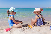 Two sister girls in swimsuits and caps playing on the beach with toys and sand on a sunny summer day. Fun family vacation at the sea.  Kids activity outdoors