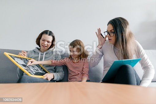 istock Two sister girls talking with young woman family psychologist, children sitting in office 1092534426
