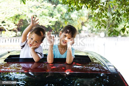 972962180istockphoto Two sister smiling out of car sunroof. Happiness and innocence action. 939653580
