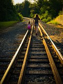 Two sisters, a teenager and a 5-6 year old, holding hands and walking down the railroad tracks. The girls are camera unaware. Photo taken in Wisconsin, USA.