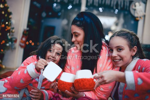 Two Sisters and Mother Drinking Hot Beverage Under Christmas Tree