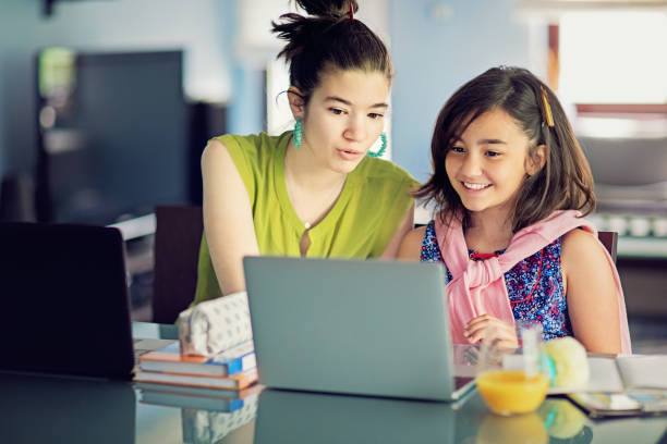 Two sisters are e-learning and video conferencing at home stock photo
