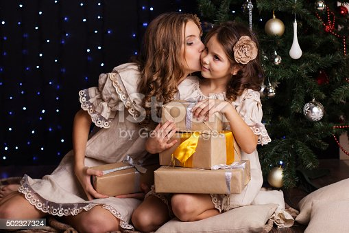 1061876006istockphoto Two sisters are sharing gifts near christmas tree 502327324