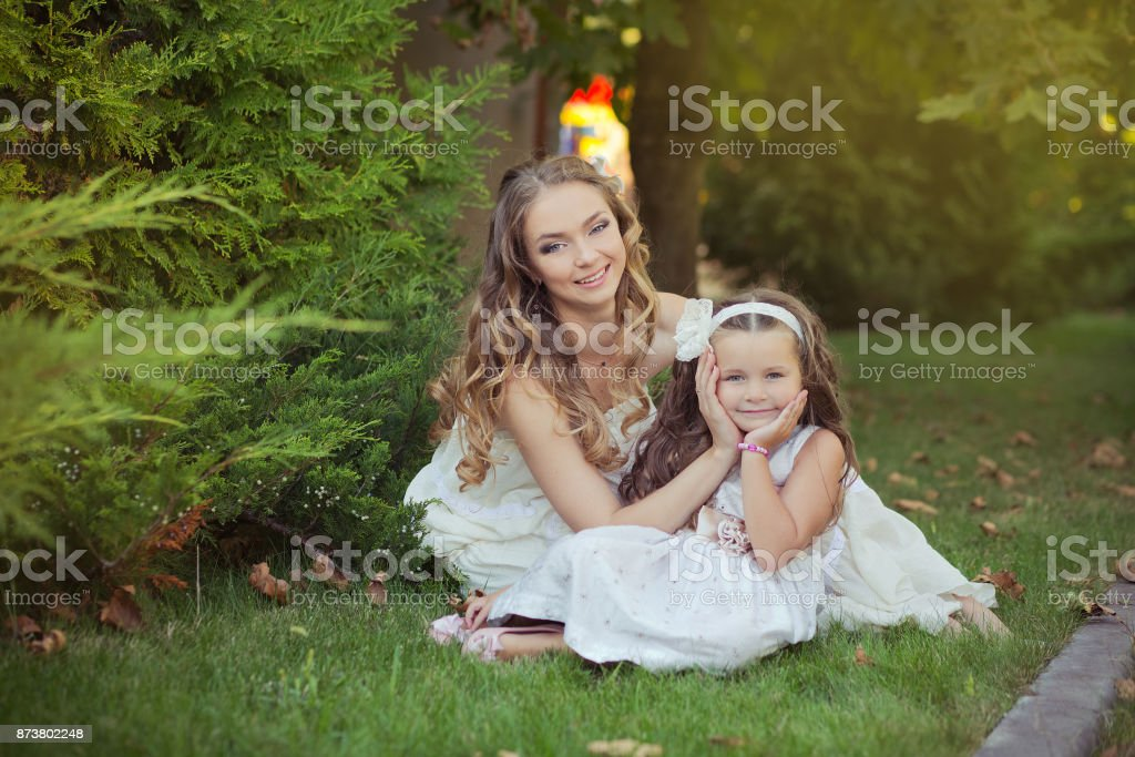 Two sisters blond chestnut blue eyes lady girls posing together summer sunny day evening dressed in white airy dinner party formal clothes on fresh spring grass garden stock photo