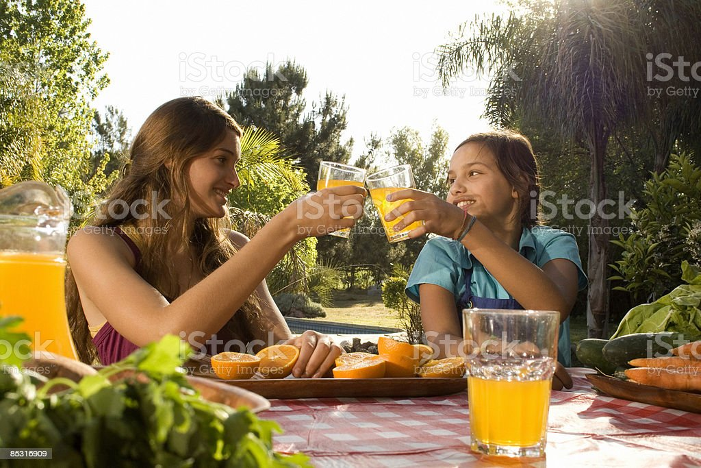 Two sisters celebrating the orange juice they made royalty-free stock photo
