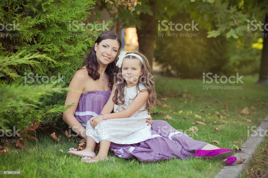 Two sisters friends chestnut brunette blue eyes woman girls posing together summer sunny day evening dressed in white purple airy dinner party formal clothes on fresh spring grass garden happy smiling stock photo