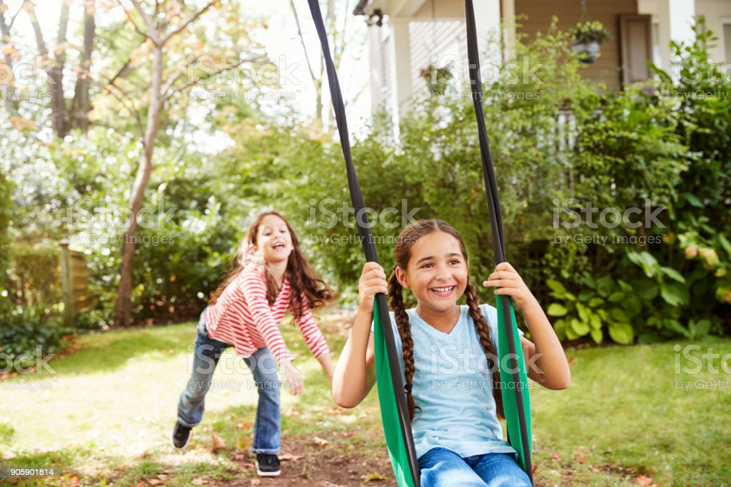 Two Sisters Having Fun On Garden Swing At Home