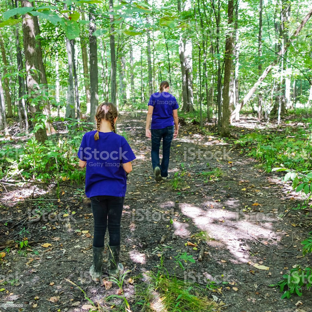 Two Sisters Hiking on a Pathway Through the Woods stock photo
