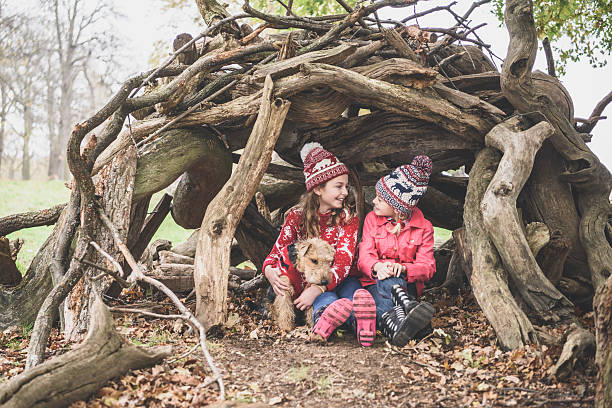 two sisters in winter clothes in log den with dog - forest animals stock photos and pictures