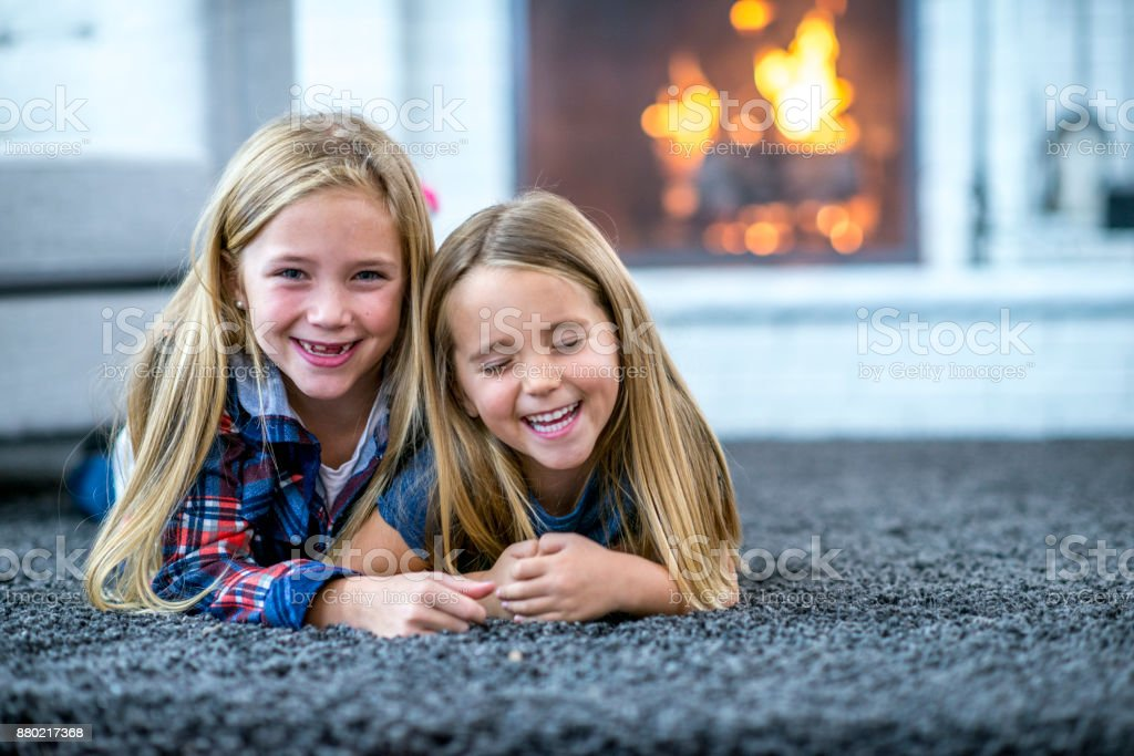 Two Sisters Lying On The Floor stock photo